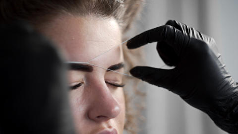 Removing small hairs from face with thread in beauty salon, depilation with Footage