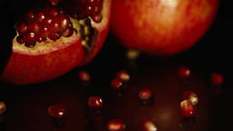 Two bright tasty big pomegranates on a black table. Opened grenade. HD Footage