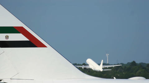 Close-up of Boeing 747 fuselage and airplane taking off at the background Live Action