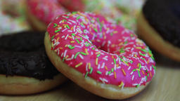 Assorted multicolored donuts lie on the table. Close-up Footage