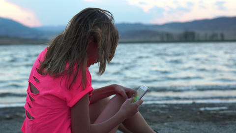 Little girl is playing on the phone Stock Video Footage