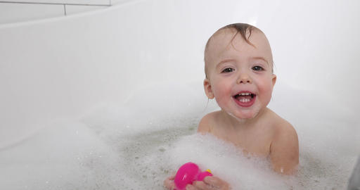 baby boy taking bath and playing with toys Footage