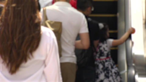 SHINJUKU, TOKYO, JAPAN - CIRCA MAY 2018 : BACK SHOT of PEOPLE using ESCALATOR Footage