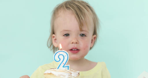 Boy looking candle on his 2 birthday cake Footage