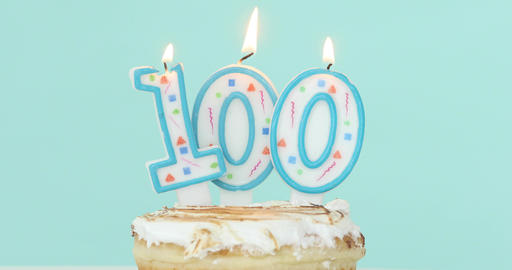 Cake with burning candles as number one hundred Footage