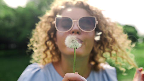 Attractive woman in sun glasses blows the dandelions and they fly away on the Footage