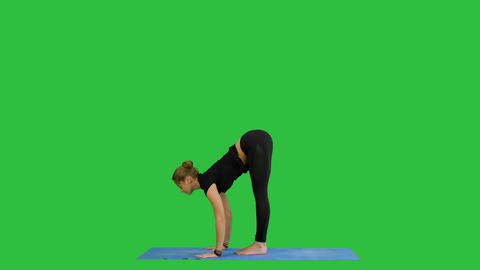 Young woman doing yogic sun salutation pose on mat on a Green Screen, Chroma Key Footage