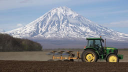 Modern tractor plowing rough land on agricultural field on background of volcano Footage