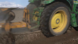 Modern tractor ploughing rough land on farming field. Farm work on sunny weather Footage