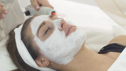 Close up darsonvalization girl face with clay mask in saloon. Cosmetic procedure Footage