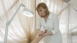 Professional cosmetologist waxing wrist girl hand in beauty saloon. Medium shot Footage
