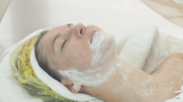 Adult woman face with some clay white mask in beauty saloon. Cosmetic procedure Live Action