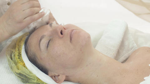 Cosmetologist wipe out woman face by napkin after cosmetic mask in beauty saloon Live Action