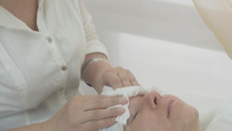 Cosmetologist wipe off woman face by napkin after cosmetic mask in beauty saloon Live Action