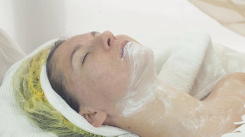 Cosmetologist wipe out mask out woman face and neck by napkin in beauty saloon Live Action