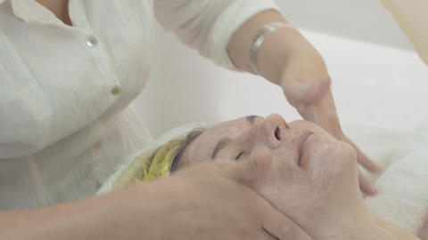 Cosmetologist put moisturizing cream on woman face in beauty saloon. Skincare Live Action
