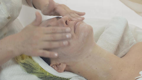 Cosmetologist rub moisturizing cream in woman face in beauty saloon. Skincare Live Action
