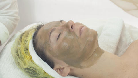Woman face with green clay cosmetic mask in beauty saloon. Skincare. Cosmetology Live Action