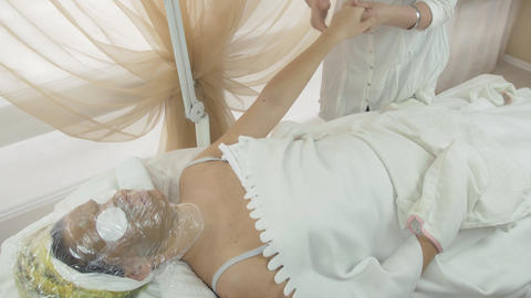 Masseuse make massage of left woman hand in beauty saloon. Thermo mask on face Footage
