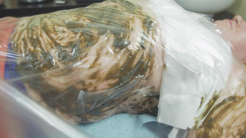 Fat woman lie with seaweed mixture on stomach, covered thermofilm. Spa wrapping Footage
