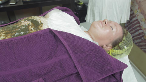 Fat adult woman lie in beauty saloon, covered by thermofilm. Seaweed wrapping Footage