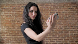Young charming brunette girl is making selfie on her smartphone, communication Footage