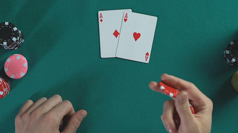 Man's hand holding poker chips, pair of aces cards, male thinking about bet Footage