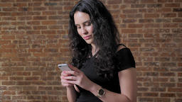 Young beautiful brunette girl surfs her smartphone, watching at camera, brick Footage