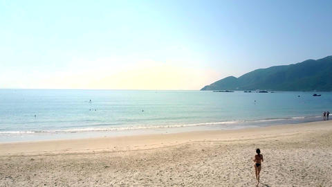 slim girl runs on beach to water edge Footage