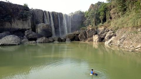asian man pulls fishing net among waterfall lake Footage