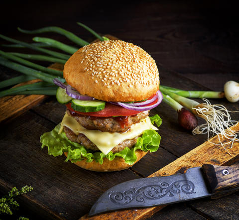 double cheeseburger with vegetables and cheese, white round bun Photo