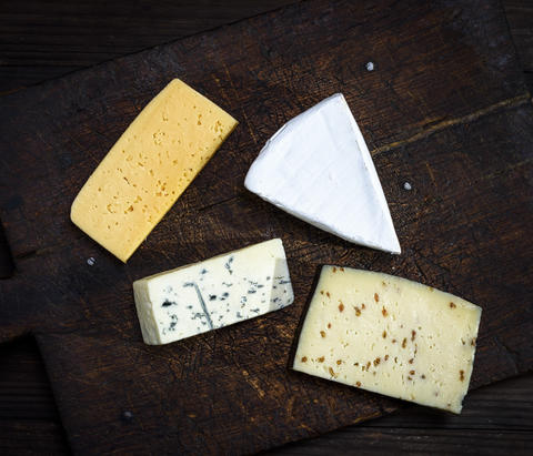 pieces of different cheeses on a brown wooden board フォト