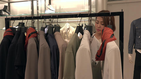 Happy Asian Woman Looking At Clothes Rack In Fashion Shop Live Action