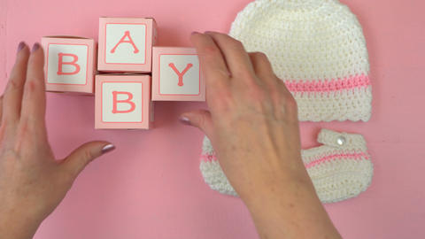4k Baby girl nursery clothing and accessories overhead on pink wood table flat Footage