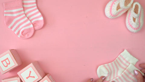 4k Baby girl nursery clothing and accessories overhead on pink wood table layout Footage