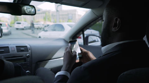 Afro-American businessman going to meeting, looking through questions on phone Footage