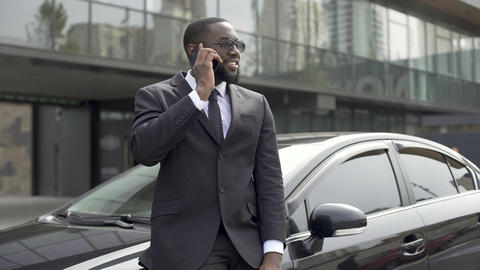 Successful man in expensive suit communicating on phone, standing near his car Footage