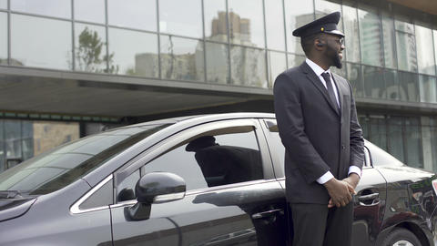 Smiling African-American taxi service driver expecting client near luxury car Live Action