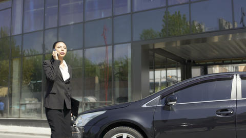 Business lady hurrying to meeting with client, solving questions by phone Footage