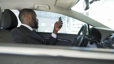 Driver waiting for boss, bored scrolling news application on his smartphone Footage