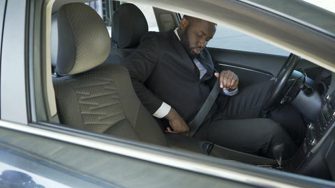 Afro-American man in expensive suit fastening and turning on ignition of his car Footage
