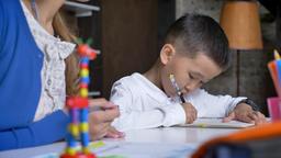 Asian little boy writing homework while mother explaining something to him Footage
