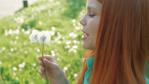 Beauty Young Woman with red hair Blowing Dandelion Wishing Joy Concept Footage
