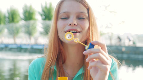Girl with red hair blowing soap bubbles Footage