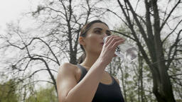 Young fit girl is drinking water in park in summer, healthy lifestyle, sport Footage