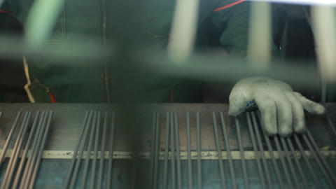 Electrodes for welding on the conveyor. Worker on the conveyor straightens the Footage