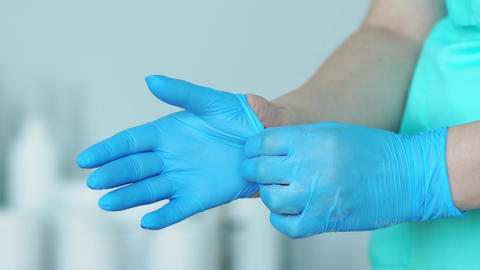 Close-up of the doctor wearing rubber gloves Live Action