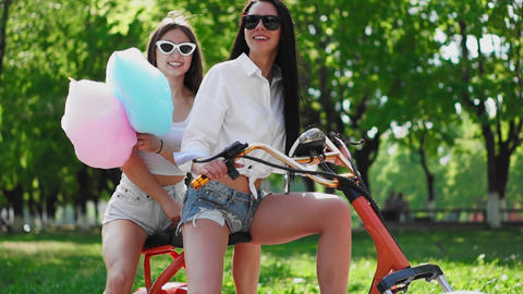 Sexy girls with sweet cotton in short shorts ride an electric scooter in the Live Action