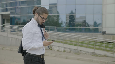 Young businessman with glasses and ponytail in suit holding jacket over his Footage