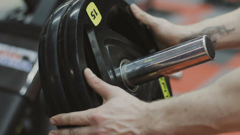 Transition shot of determined muscular man putting heavy plates on barbell and Live Action